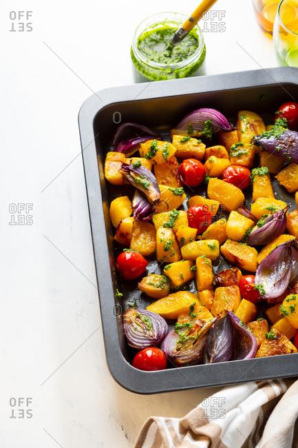 Baking sheet full with baked vegetables on white surface