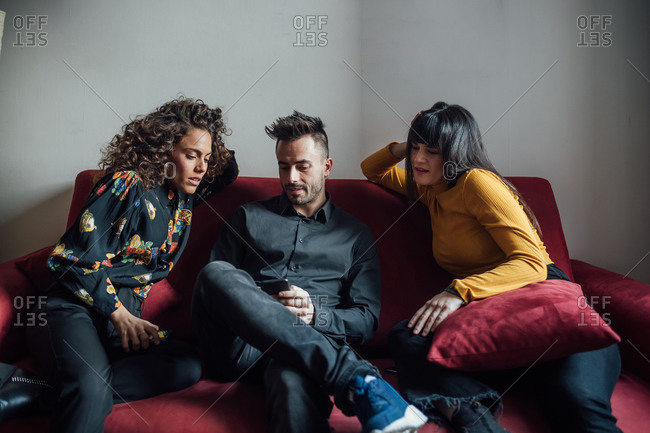Friends using smartphone on sofa
