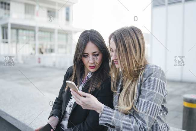 Two young businesswomen sitting outside office building looking at smartphones, Turin, Piemonte, Italy