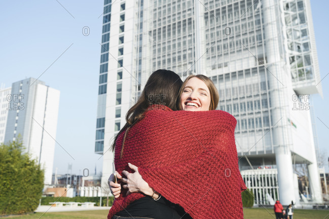 Two young women hugging outside skyscraper, Turin, Piemonte, Italy