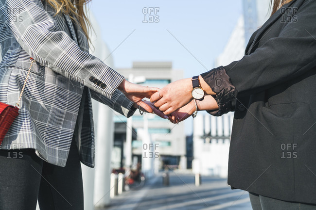 Two young women holding hands outside office building,  cropped, Turin, Piemonte, Italy