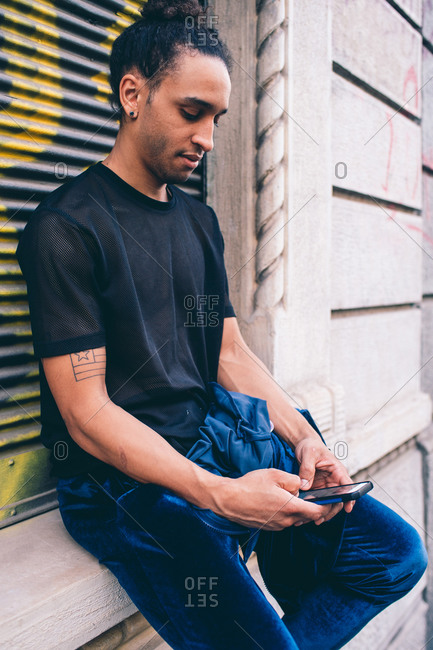 Young man using smartphone on window ledge of building