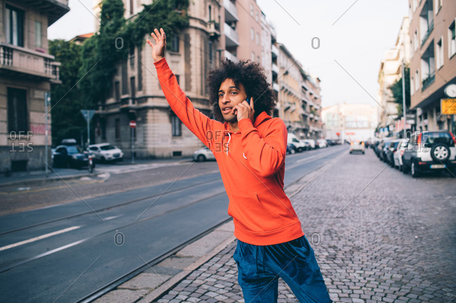 Young man hailing cab in city, Milano, Lombardia, Italy