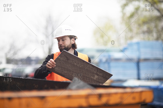 Mid adult male construction worker putting waste into waste skip