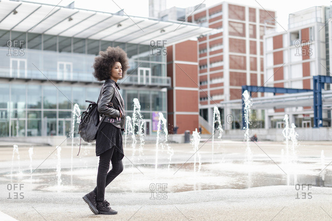 Cool young woman with afro hair on city concourse, full length