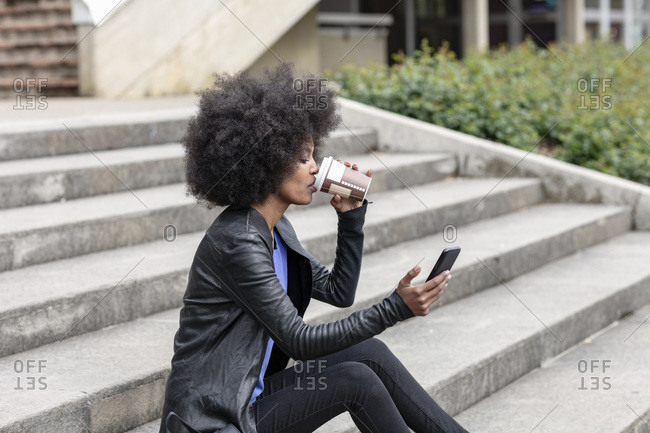 Young woman with afro hair sitting on city stairway, drinking takeaway coffee and looking at smartphone