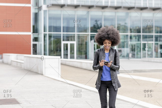 Young woman with afro hair in city, using smartphone touchscreen