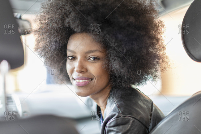 Happy young woman with afro hair in car passenger seat, portrait