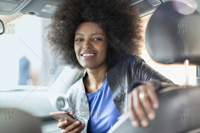 Happy young woman with afro hair in car passenger seat holding smartphone, portrait