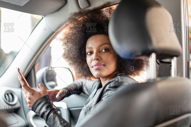 Young woman with afro hair in car passenger seat holding smartphone, portrait