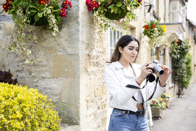 Young woman on village street reviewing photos on digital camera, Cotswolds, England