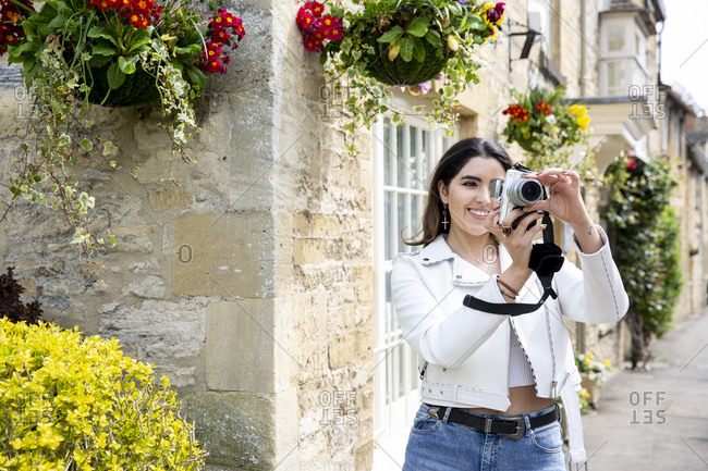 Young woman on village street photographing with digital camera, Cotswolds, England