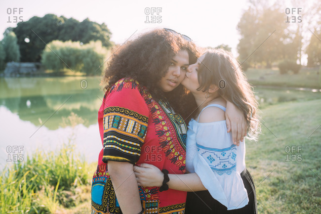 Friends hugging and kissing on cheek in park