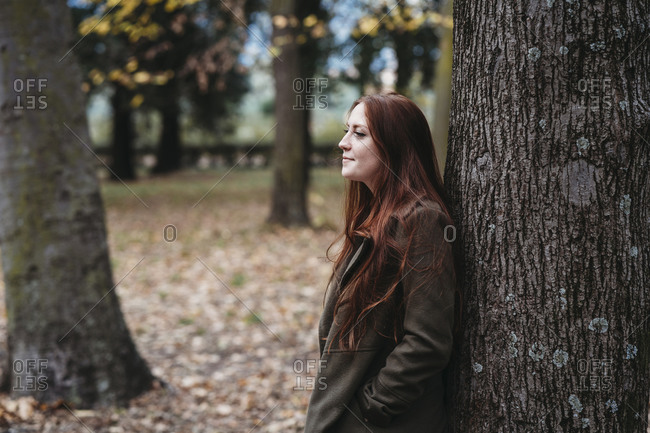 Young woman with long red hair leaning against tree trunk in autumn park
