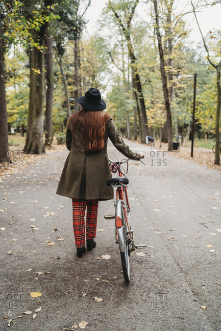 Young woman with long red hair pushing bicycle in autumn park, rear view full length, Florence, Tuscany, Italy