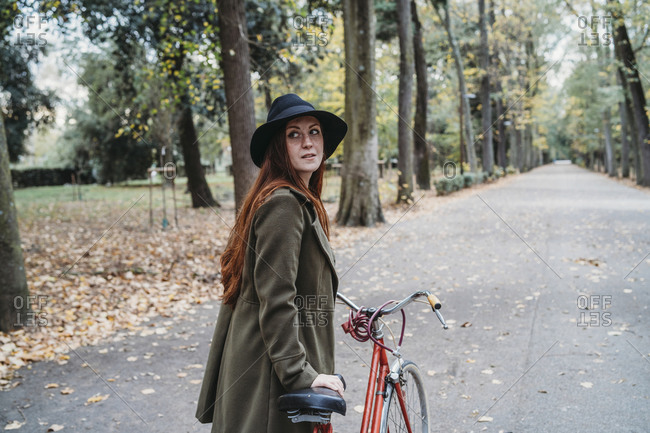 Young woman with long red hair looking over her shoulder while pushing bicycle in autumn park, Florence, Tuscany, Italy