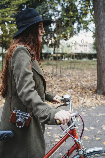 Young woman with long red hair pushing bicycle in autumn park