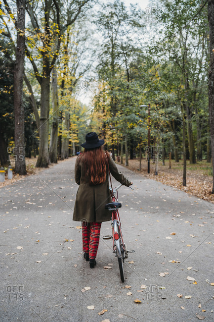 Young woman with long red hair pushing bicycle in tree lined  autumn park, rear view, Florence, Tuscany, Italy