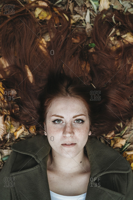 Young woman with long red hair lying amongst autumn leaves, overhead portrait