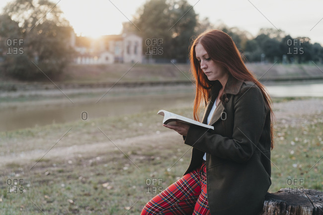Young woman with long red hair sitting on tree stump reading book on riverside at sunset, Florence, Tuscany, Italy