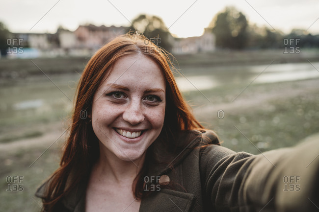 Young woman with long red hair smiling for selfie on riverside, personal perspective, Florence, Tuscany, Italy