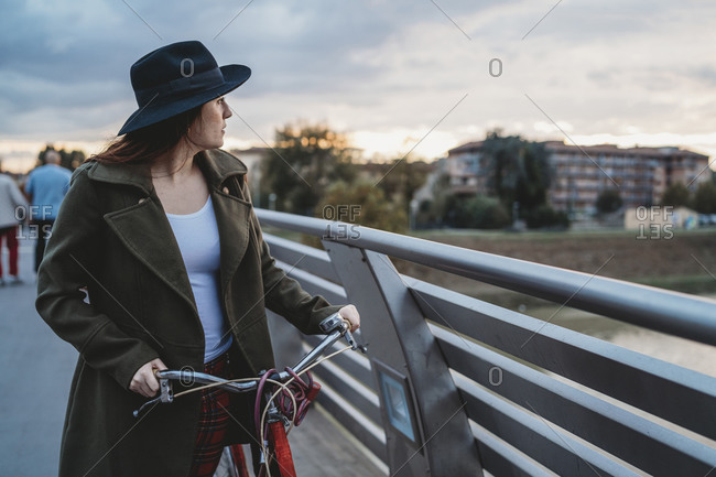Young woman with bicycle looking out from footbridge at dusk, Florence, Tuscany, Italy