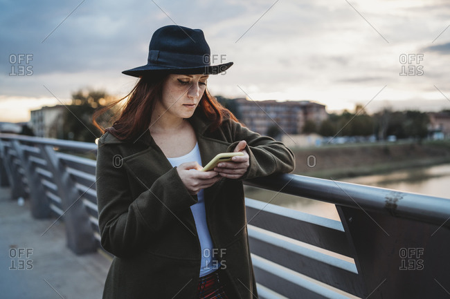 Young woman with long red hair on footbridge looking at smartphone at dusk, Florence, Tuscany, Italy