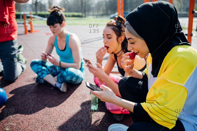 Calisthenics class at outdoor gym, young women sitting looking at smartphones and eating fruit