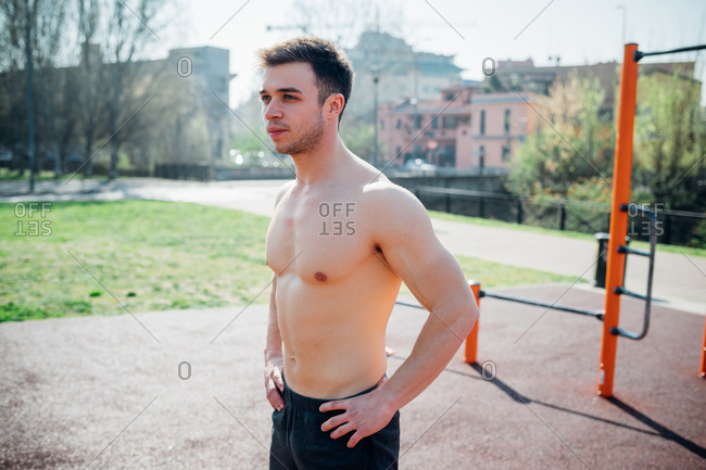 Calisthenics at outdoor gym, bare chested young man taking a break