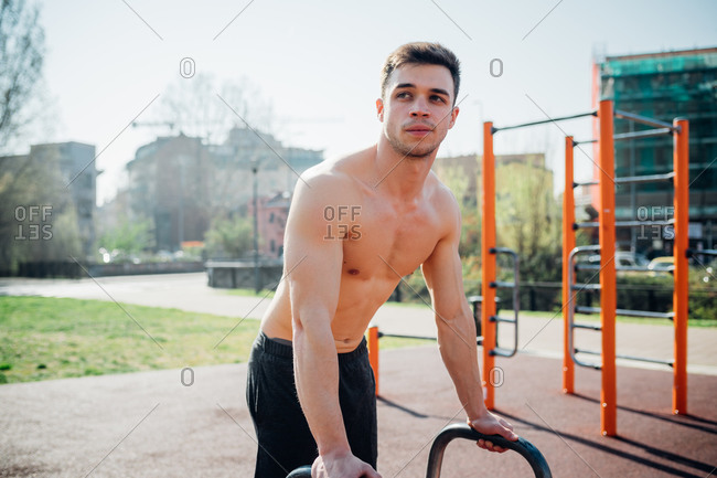 Calisthenics at outdoor gym, bare chested young man preparing to use exercise equipment