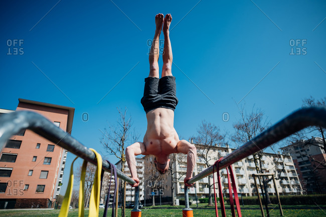 Calisthenics at outdoor gym, bare chested young man doing handstand on parallel bars, low angle view