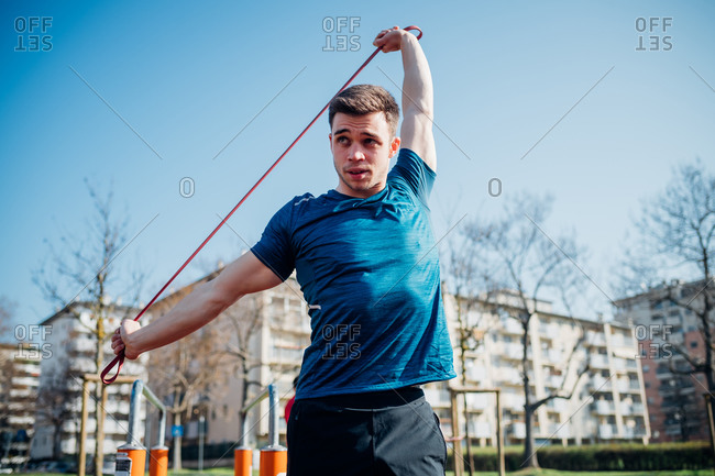 Calisthenics at outdoor gym, young man stretching resistance band