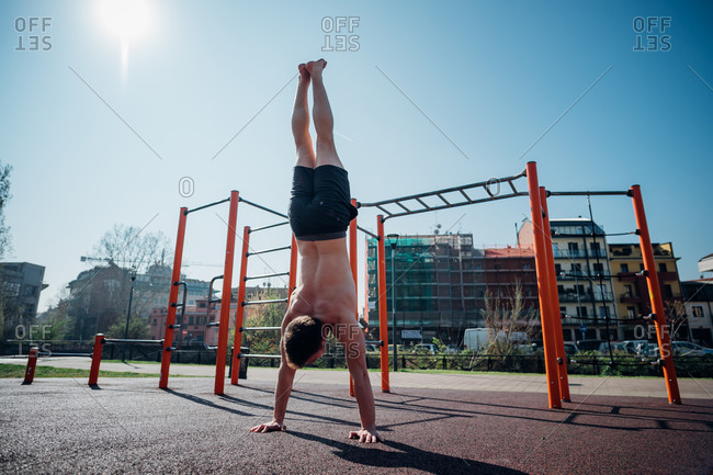 Calisthenics at outdoor gym, young man doing handstand, rear view