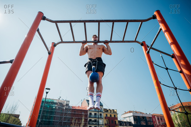 Calisthenics at outdoor gym, young man doing pull ups on exercise equipment with kettlebell on waist harness