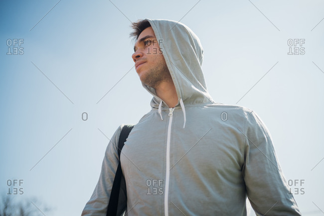 Calisthenics in park, young man in hoody against blue sky