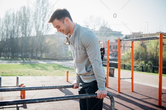 Calisthenics at outdoor gym, young man on parallel bars