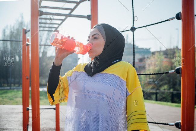 Calisthenics class at outdoor gym, young woman drinking from water bottle