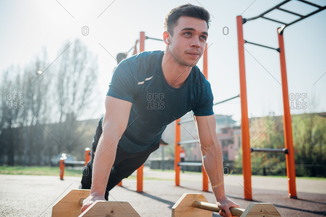 Calisthenics at outdoor gym, young man doing push ups on exercise equipment