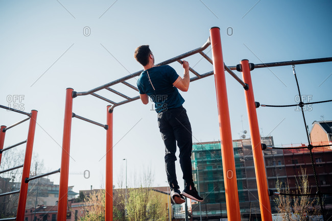 Calisthenics at outdoor gym, young man doing pull ups on exercise equipment, rear view