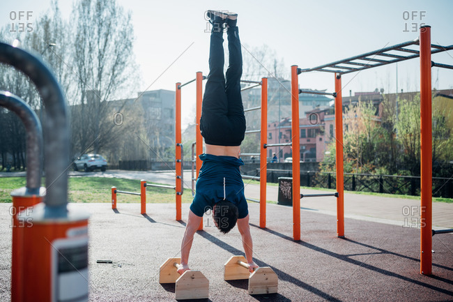 Calisthenics at outdoor gym, young man doing hand stand on exercise equipment, rear view