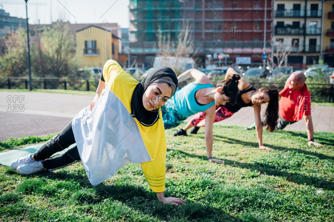 Calisthenics class at outdoor gym, women and man practicing sideways yoga position