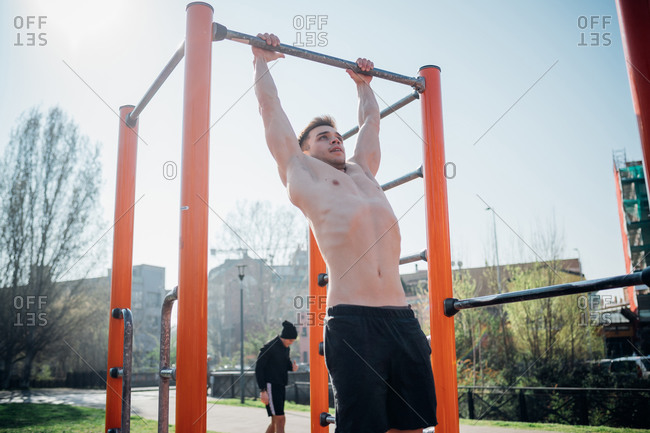 Calisthenics at outdoor gym, bare chested young man hanging from exercise equipment