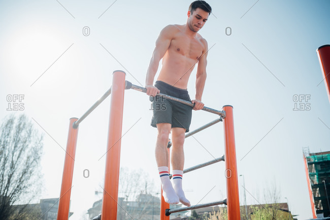 Calisthenics at outdoor gym, bare chested young man doing push up on exercise equipment