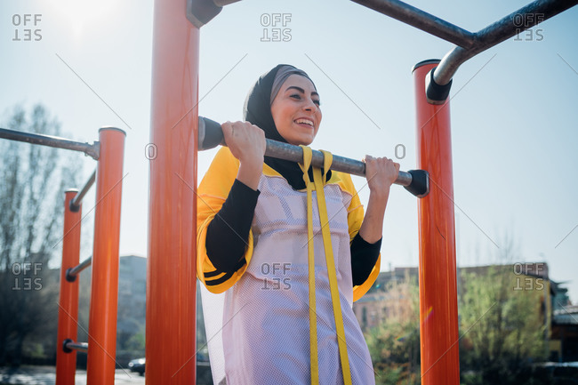 Calisthenics at outdoor gym, young woman doing pull up on exercise equipment