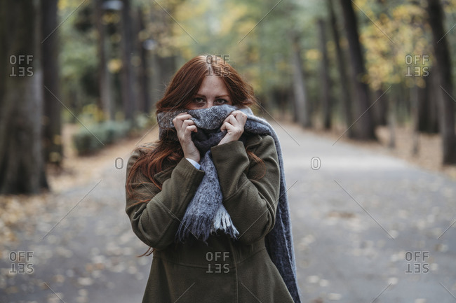 Young woman with long red hair in autumn park covering mouth with scarf, portrait