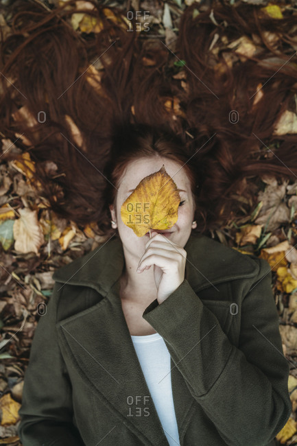 Young woman with long red hair lying amongst autumn leaves and covering face with autumn leaf, overhead portrait