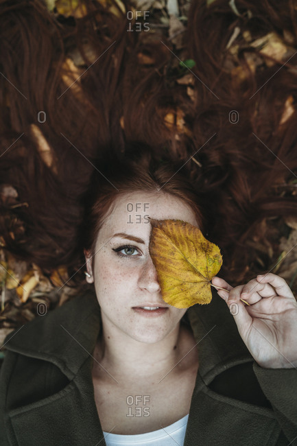 Young woman with long red hair lying amongst autumn leaves and covering eye with autumn leaf, overhead portrait