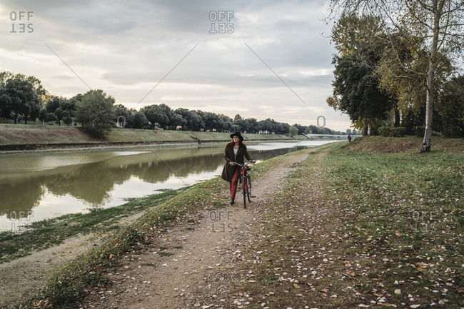 Young woman with long red hair pushing bicycle on riverside, full length, Florence, Tuscany, Italy