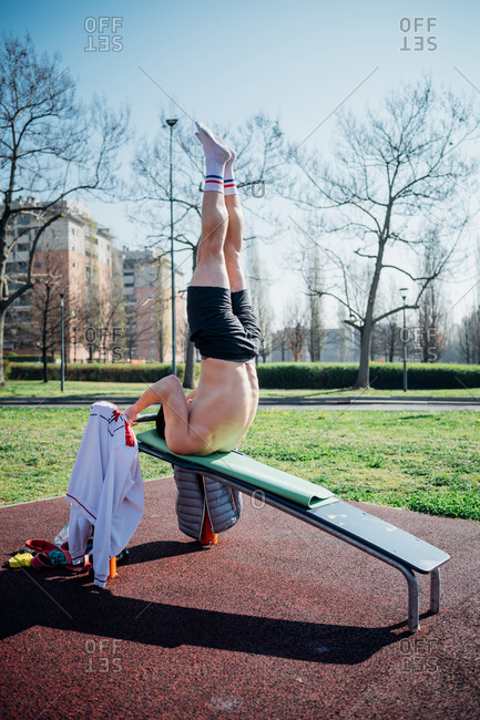 Calisthenics at outdoor gym, young man upside down on weights bench