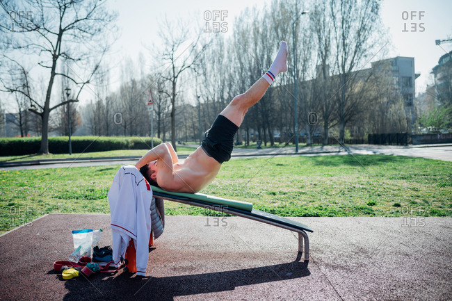 Calisthenics at outdoor gym, young man on weights bench with legs raised